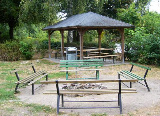 Im Vordergrund befindet sich eine Feuerstelle mit 4 Bänken. Im Hintergrund sehen wir ein gemütlicher, idyllischer Pavillon im Garten, der Schutz bietet vor Sonne und Regen.