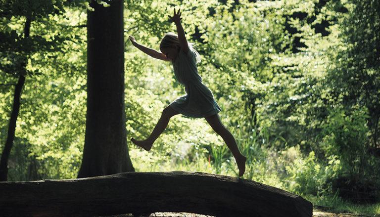 Junges Mädchen in einem Kleid im Wald, die auf einem umgekippten Baumstamm zu einem Radschlag ansetzt.